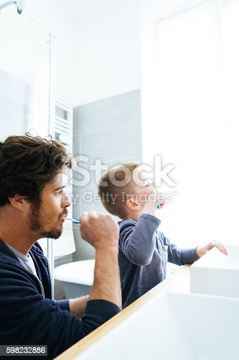 185211538istockphoto Father And Son Brushing Their Teeth 598232886