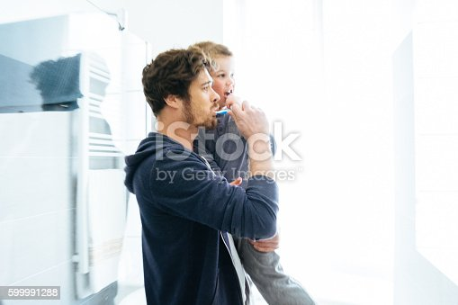 185211538istockphoto Father And Son Brushing Their Teeth 599991288