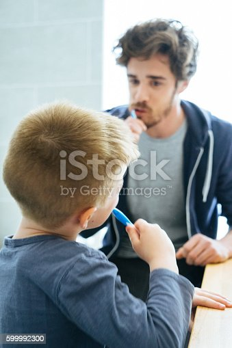 185211538istockphoto Father And Son Brushing Their Teeth 599992300