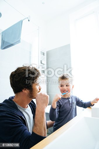 185211538istockphoto Father And Son Brushing Their Teeth 610660156