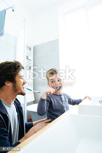 185211538istockphoto Father And Son Brushing Their Teeth 614211426