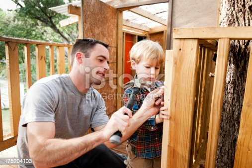 A father and son build a tree house with hammer and nails.  Please see my portfolio for more images from this series.