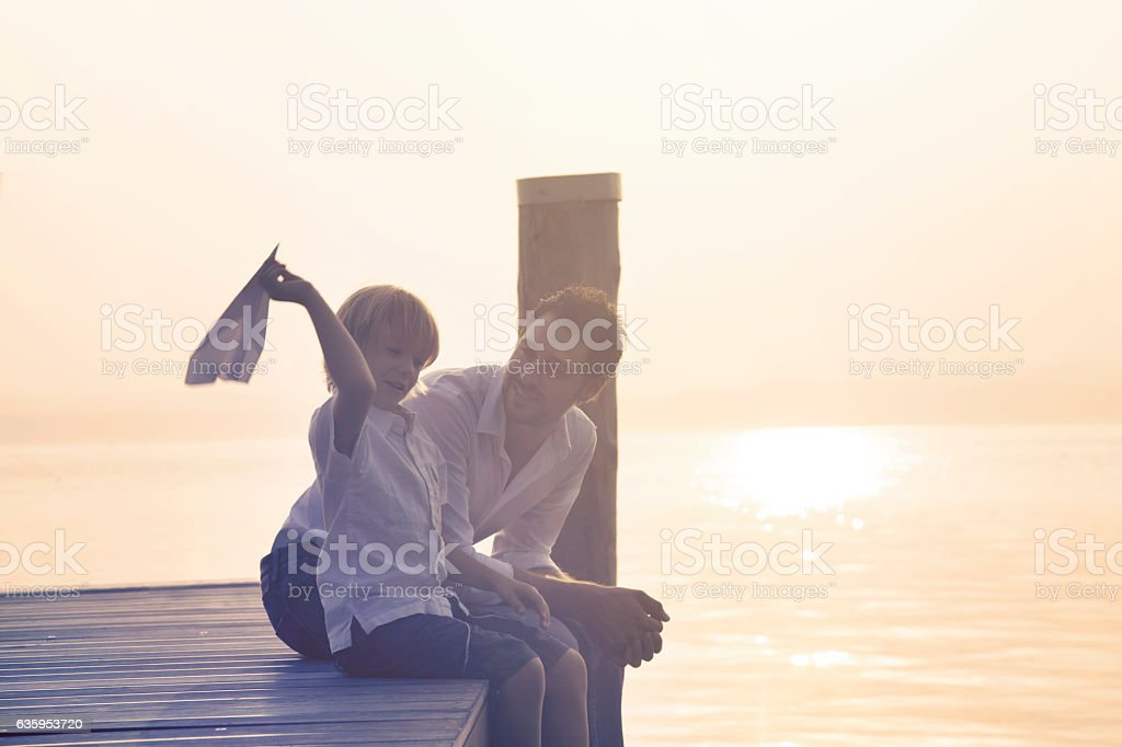Father and son building together a paper airplane stock photo