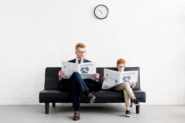 father and son businessmen wearing eyeglasses and reading newspapers on sofa - pais e filhos imagens e fotografias de stock