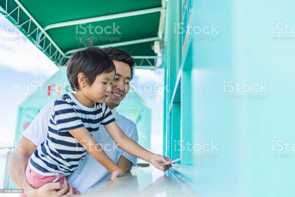 Father and son buys admission tickets stock photo