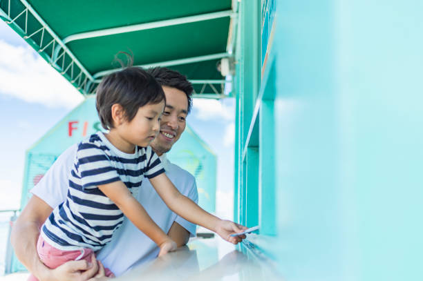 Father and son buys admission tickets Japanese family enjoying vacation in guam admit stock pictures, royalty-free photos & images