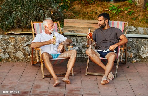 Senior man and mid adult man relaxing by the pool in back yard by the swimming pool. Sitting in lounge chairs and drinking beer.