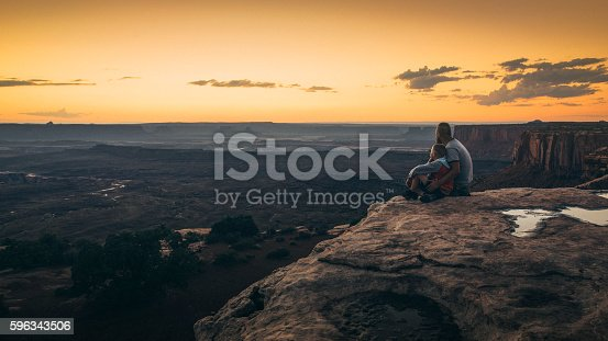 Father and son sitting on the edge of cliff overlooking vast landscape at Grand View Point of Canyonlands National Park during sunset.
