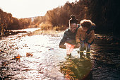 Happy successful father and son having fun fishing and catching fish in mountain river stream