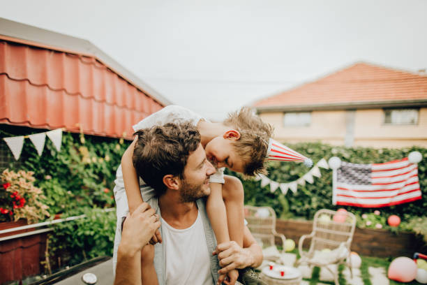 Father and son celebrating Fourth of July Photo of father and son celebrating Fourth of July in their yard family 4th of july stock pictures, royalty-free photos & images