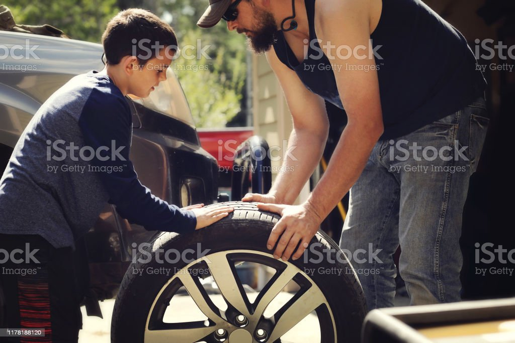 Father and son changing a tire A father and son working together to change a tire on a car. 30-39 Years Stock Photo