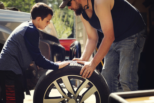 Father And Son Changing A Tire Stock Photo - Download Image Now