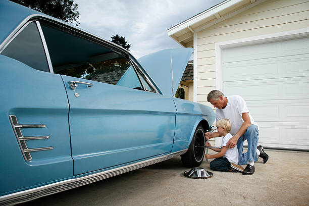 father and son changing a tire - classic cars stock photos and pictures