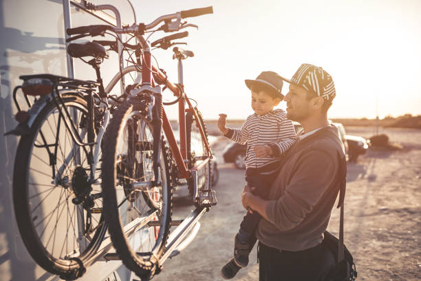 Father and son cheking bikes on motor home Father and son cheking bikes on motor home rv bike stock pictures, royalty-free photos & images