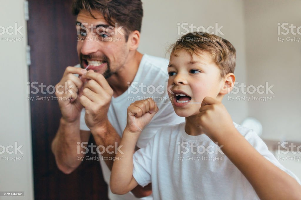 Father and son cleaning teeth with dental floss stock photo