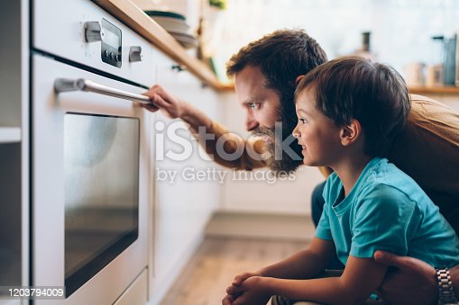 Single father with son baking at home and looking through the oven glass
