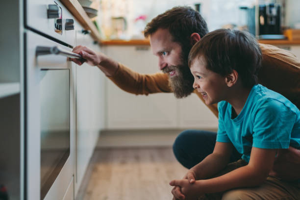 Father and son cooking dinner at home stock photo