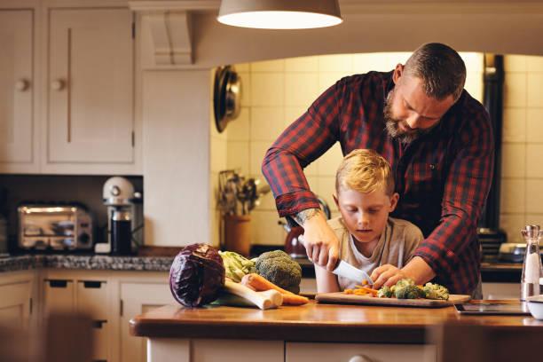 padre e hijo, cocinar los alimentos en la cocina - padre que se queda en casa fotografías e imágenes de stock
