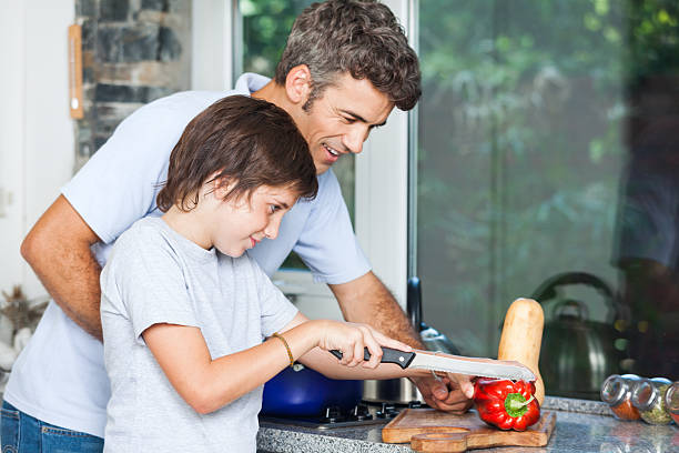 father and son cooking home kitchen, slicing stock photo