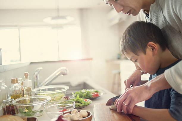 Father and son cooking together at home stock photo