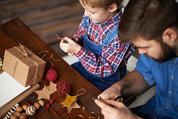 vater und sohn aus dem nähkästchen - basteln mit kindern weihnachten stock-fotos und bilder