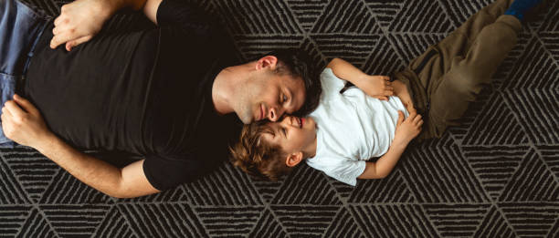 Father and Son Cuddle on the floor stock photo