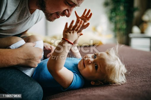 649431568 istock photo Father and son cuddling in bed 1166579830