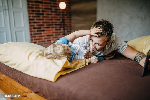 649431568 istock photo Father and son cuddling in bed 1166580844
