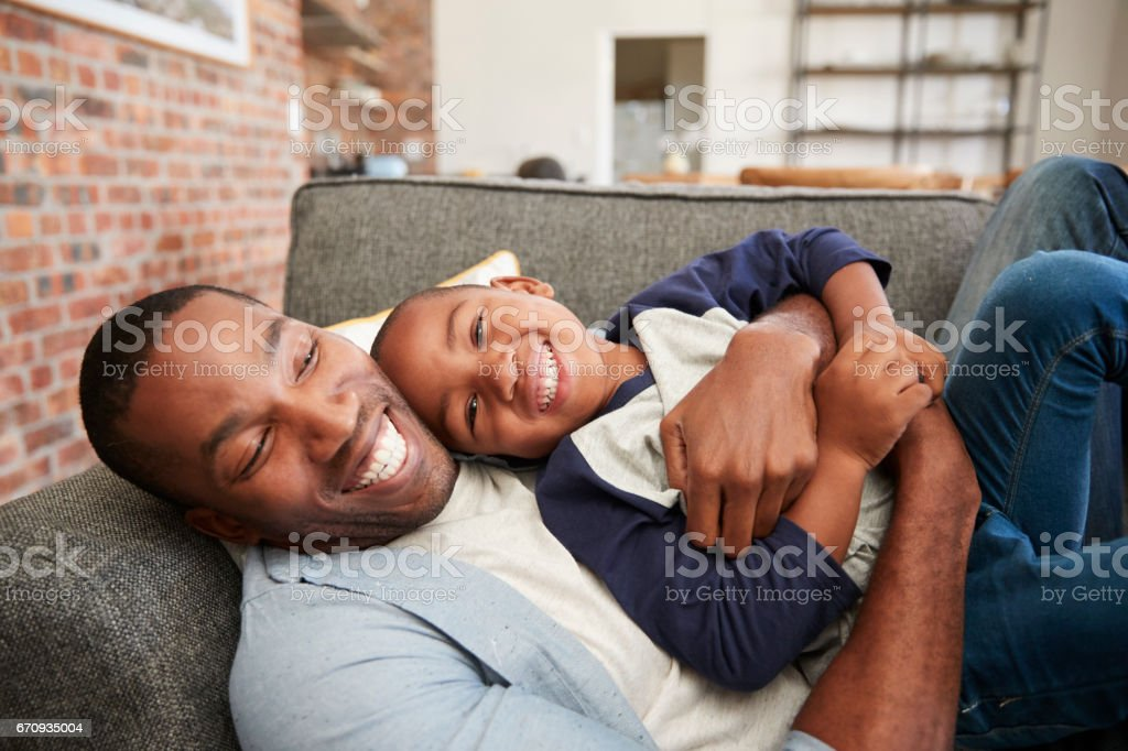 Father And Son Cuddling On Sofa Together stock photo