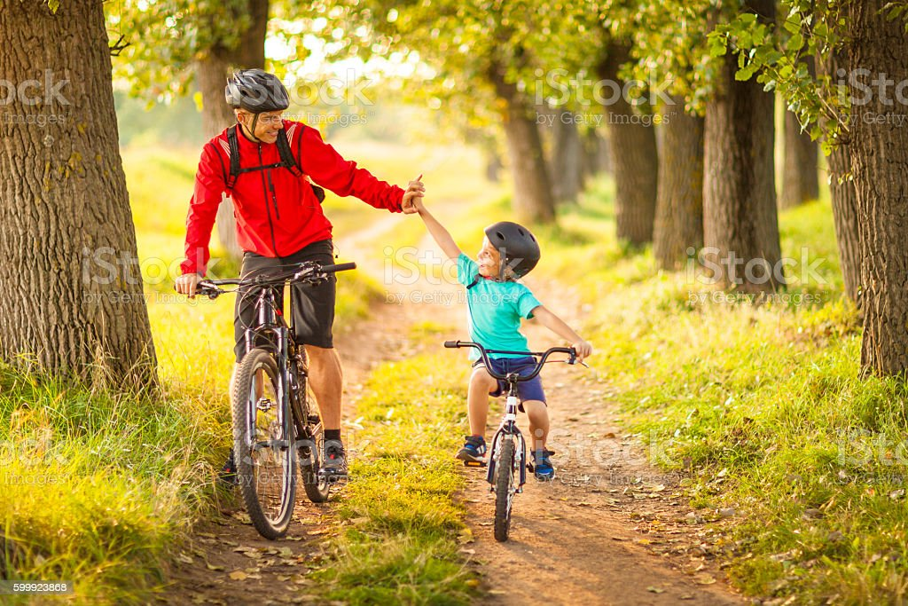Father and son cycling in the countryside stock photo