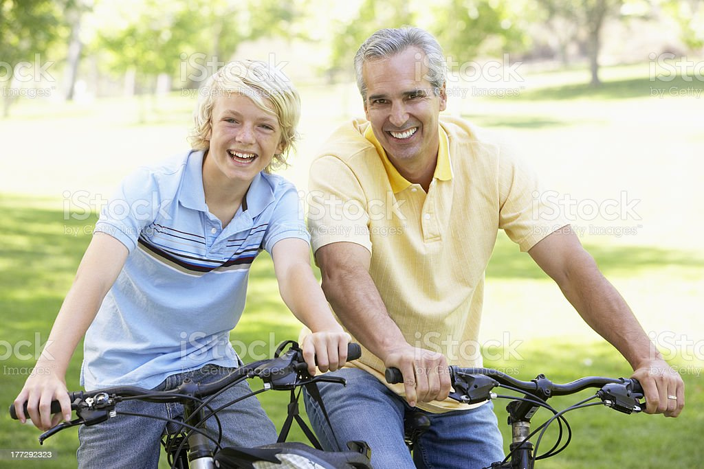 Father And Son Cycling Through A Park royalty-free stock photo