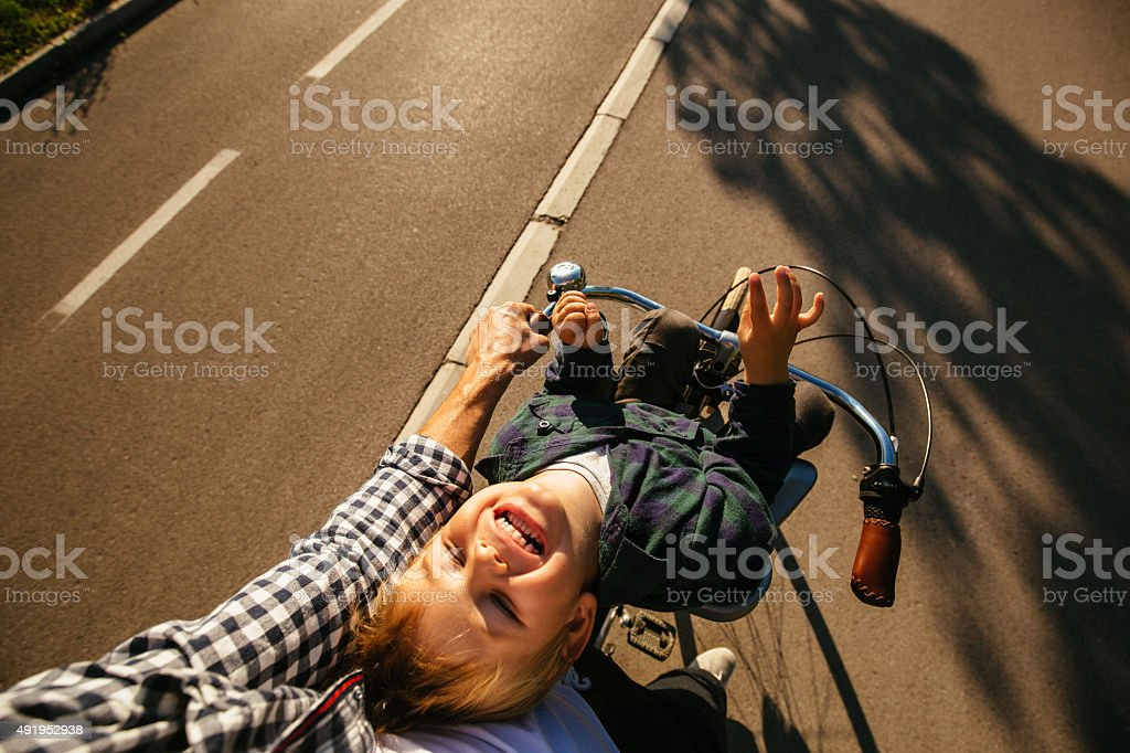 Father and son cycling together stock photo