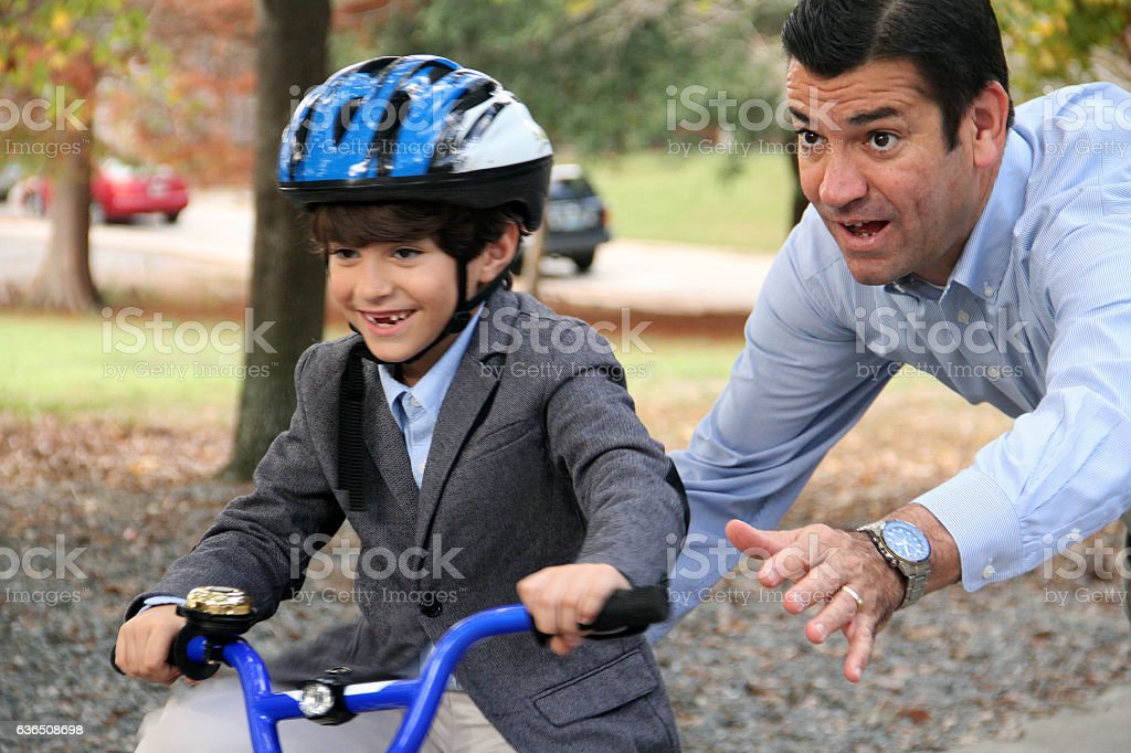 Father and son cycling with help scafolding stock photo