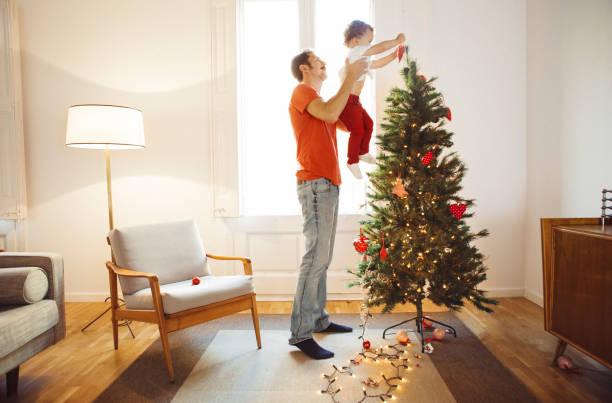 father and son decorating the christmas tree - weihnachtlich dekorieren stock-fotos und bilder