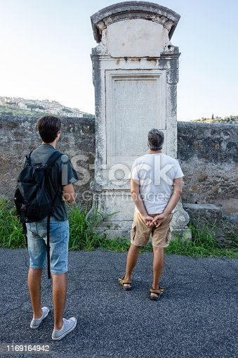 Father and Son discovering Roman Ruins in Italy, photo taken in a street of Tivoli, Lazio, where you can find many Roman Ruins in the streets of the city.