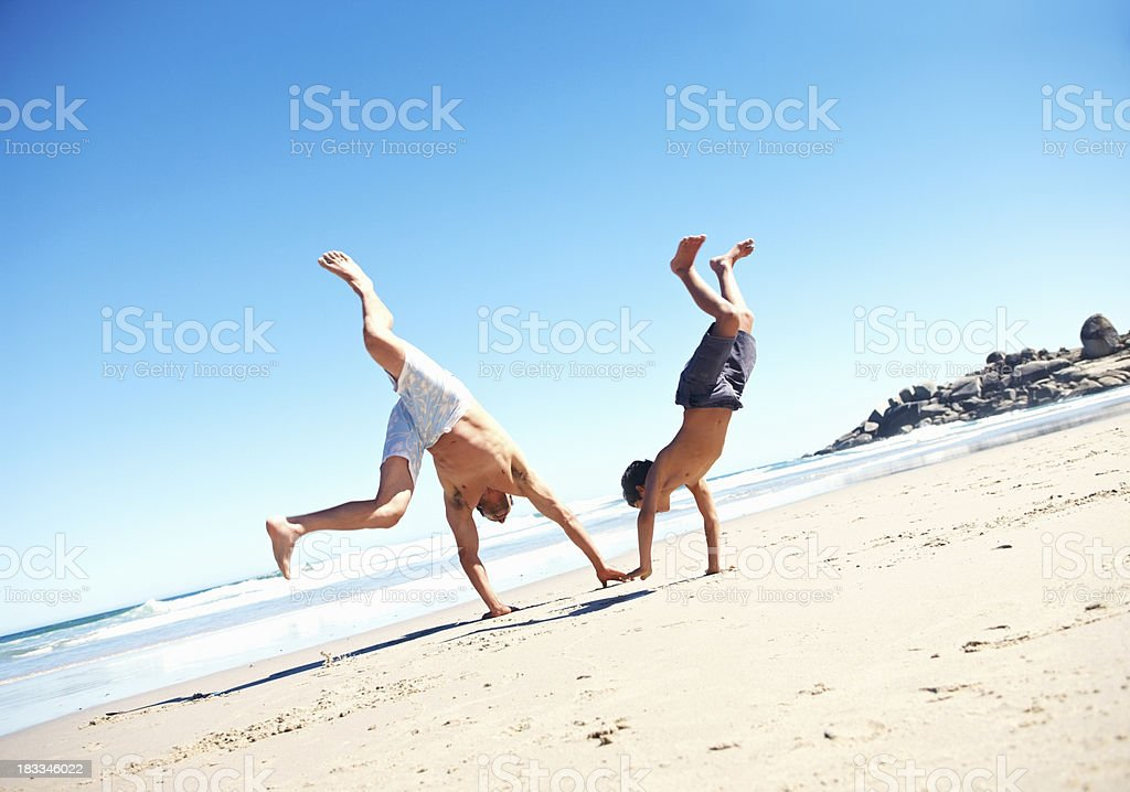 Father and son doing cartwheels on the beach stock photo