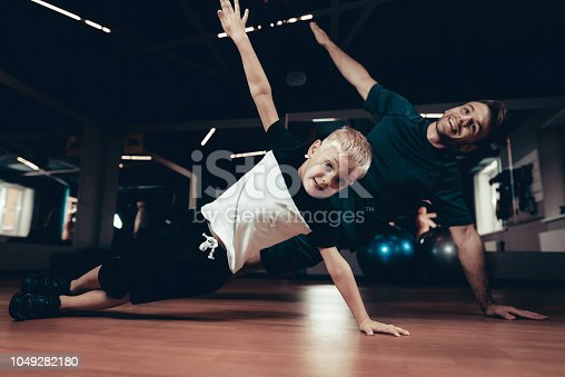 997711042istockphoto Father And Son Doing Press Exercises In The Gym. 1049282180