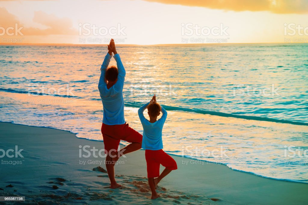 father and son doing yoga at sunset beach royalty-free stock photo