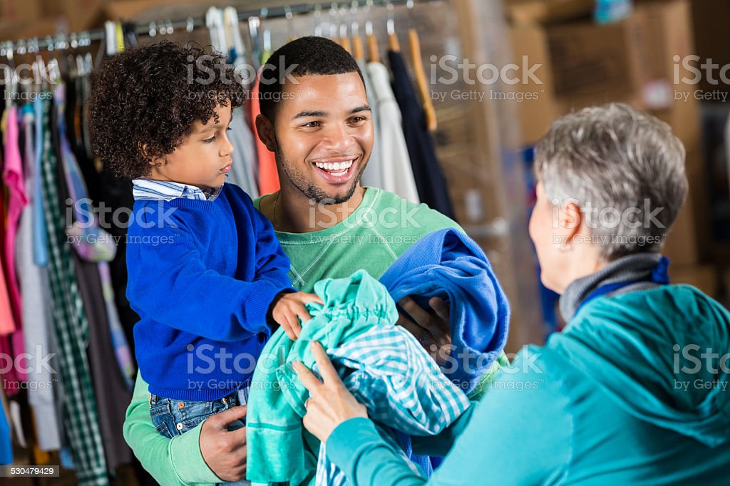 father and son donating clothing to charity distribution. Black Bedroom Furniture Sets. Home Design Ideas