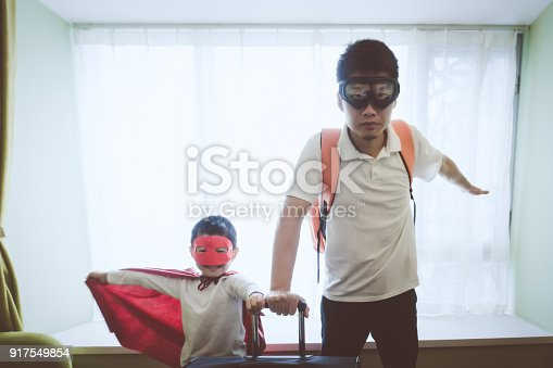 Father and son dressed superhero indoors.