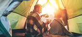 istock Father and son drink hot tea sitting together in camping tent 1168138186