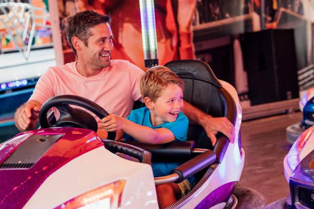 far och son kör dodgem bilar - krockad bil bildbanksfoton och bilder