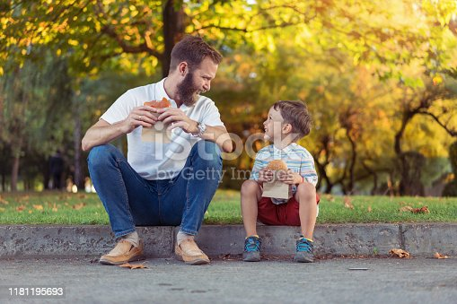 Happy father and little son eating burgers in the city park