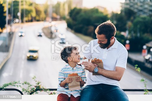 Single father with son eating hamburgers at the bridge