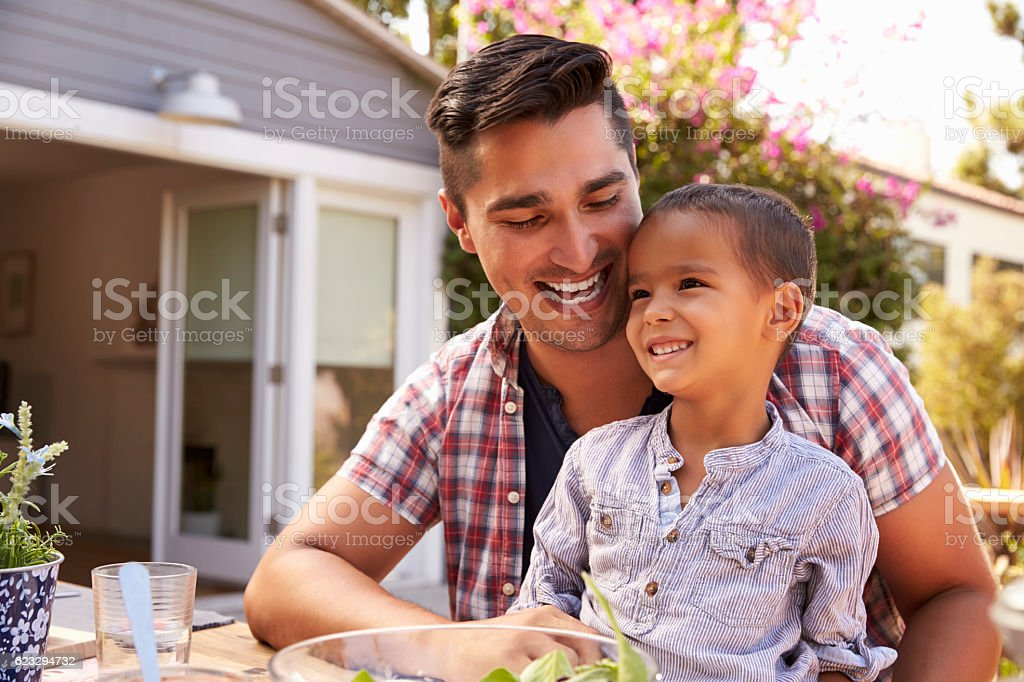 Father And Son Eating Outdoor Meal In Garden Together stock photo