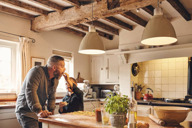 Father and son eating pizza in kitchen at home stock photo