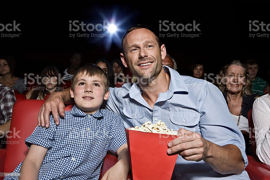 Father and son enjoying a movie stock photo