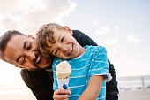 Boy eating an ice cream standing near seafront with his father. Little boy holding an ice cream cone while his father playfully tries to eat it from behind.