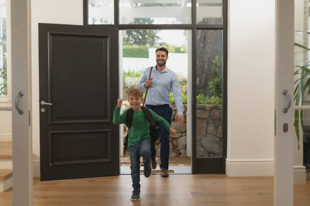 Father and son entering in a comfortable home Front view of Caucasian father and son entering in a comfortable home entering stock pictures, royalty-free photos & images