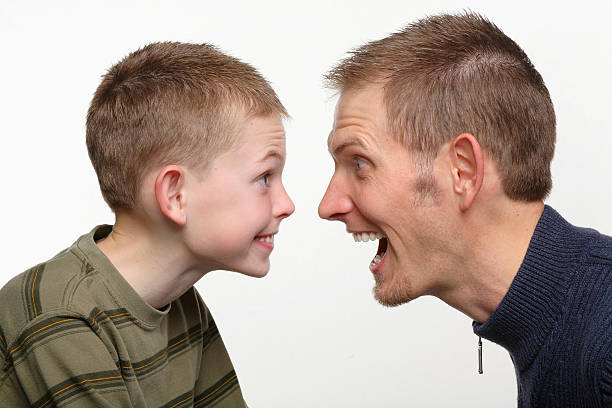Father and son facing each other, making funny faces stock photo